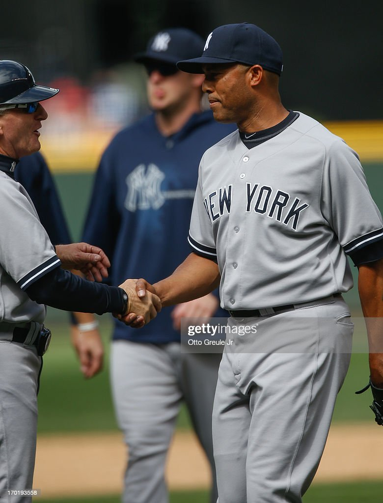 Closing pitcher Mariano Rivera #42 (R) of the New York Yankees is congratulated by first base coach Mick Kelleher #50 after defeating the Seattle Mariners 3-1 at Safeco Field on June 8, 2013 in Seattle, Washington.