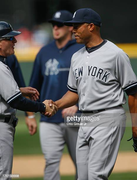 Closing pitcher Mariano Rivera of the New York Yankees is congratulated by first base coach Mick Kelleher after defeating the Seattle Mariners 31 at...