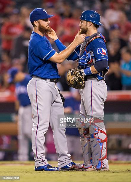 Closing pitcher Sam Dyson and catcher Jonathan Lucroy of the Texas Rangers celebrate by touching each other's beards after defeating the Los Angeles...