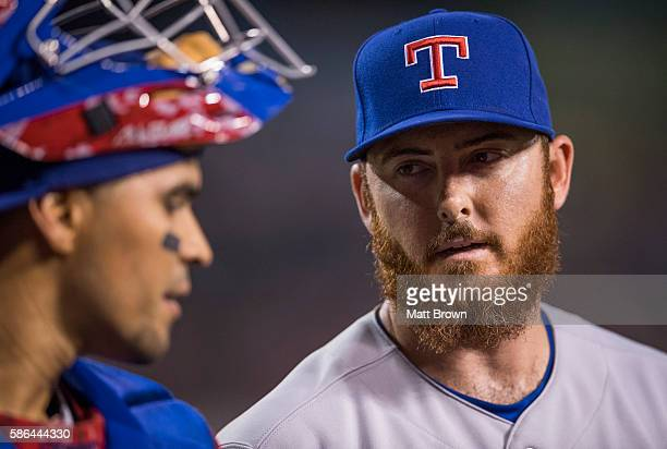Closing pitcher Sam Dyson right #47 of the Texas Rangers talks with catcher Robinson Chirinos during the eighth inning of the game against the Los...