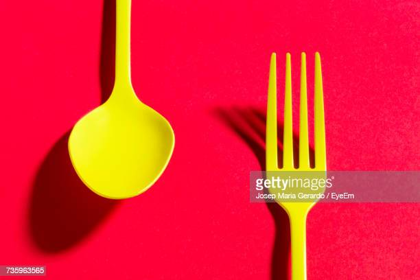 Clos-Up Of Yellow Spoon And Fork Against Red Background