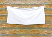 Cloth banner hanging on brick wall.