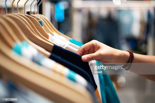 cloth handing on clothes rack  in shop - clothes rack stock pictures, royalty-free photos & images