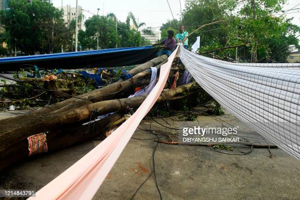 Cloth merchants standing on a fallen tree dry their damaged clothes following the landfall of cyclone Amphan on the side of a busy road in Kolkata on...
