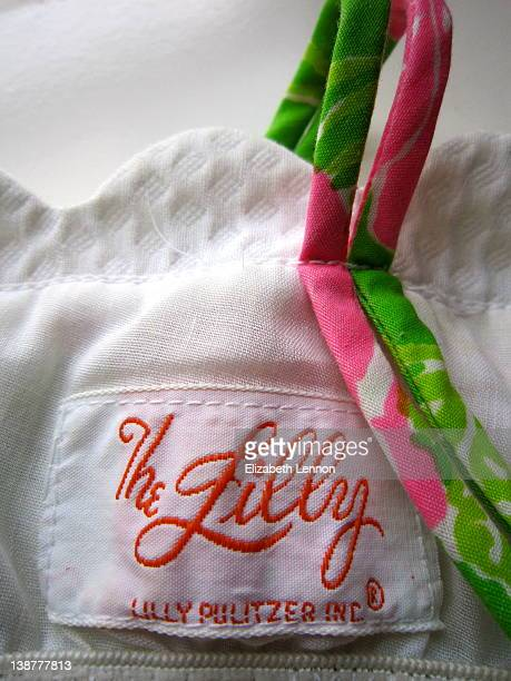 Cloth tag from inside vintage Lilly Pulitzer sun dress The Lilly logo in script writing with Lilly Pulitzer Inc below Pink and green dress strap on...