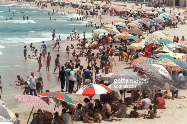Clothed men and women surrounded by children swim and relax on the beach of the Mediterranean city of Alexandria 16 June 1989 AFP PHOTO MIKE NELSON