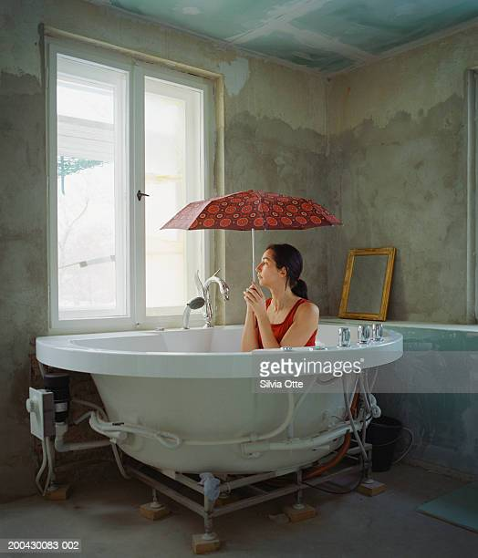 Clothed woman in tub sitting under umbrella