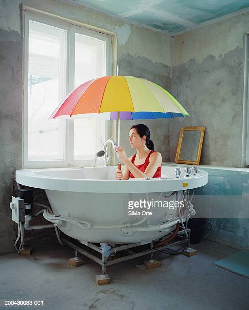 Clothed woman in tub sitting under unbrella