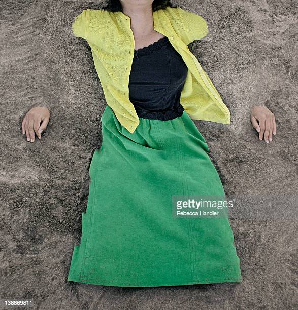 Clothed young woman buried in sand.