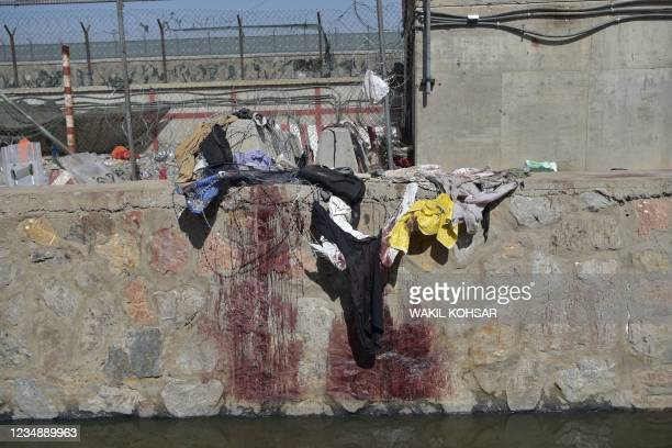 Clothes and blood stains of Afghan people who were waiting to be evacuated are seen at the site of the August 26 twin suicide bombs, which killed...