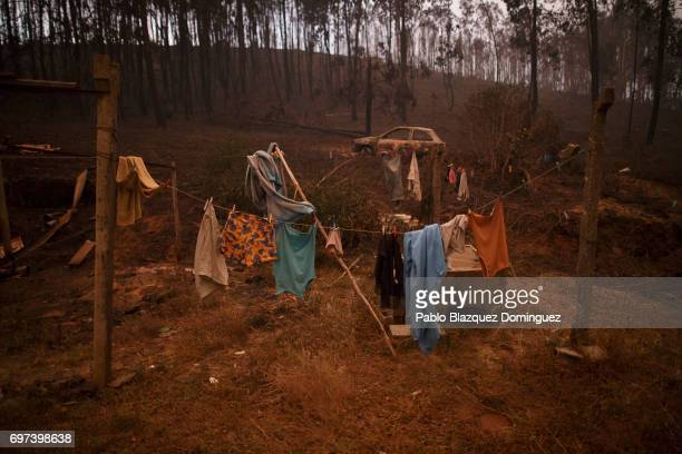 Clothes are hanging for drying next to a burned car after a wildfire took dozens of lives on June 18 2017 near Castanheira de Pera in Leiria district...