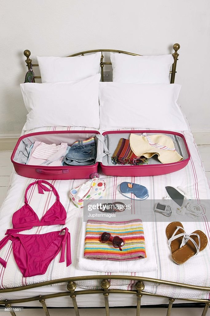 Clothes arranged by suitcase on bed : Stock Photo