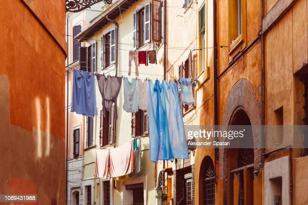 clothes drying on a rack after laundry in the narrow street, rome, italy - alley stock pictures, royalty-free photos & images