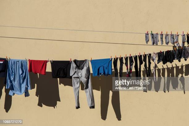 clothes drying on clothesline against wall - 物干し ストックフォトと画像