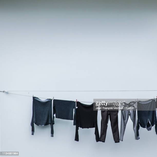 clothes drying on clothesline against white wall - 洗濯物 ストックフォトと画像