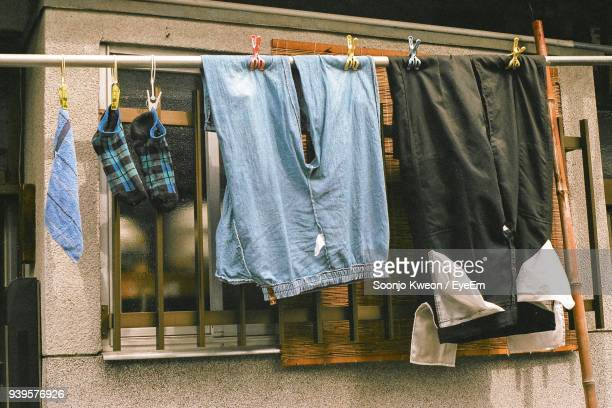 clothes drying on clothesline against window - 乾かす ストックフォトと画像