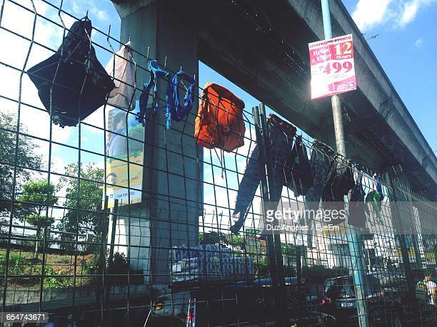 Clothes Drying On Fence Below Bridge