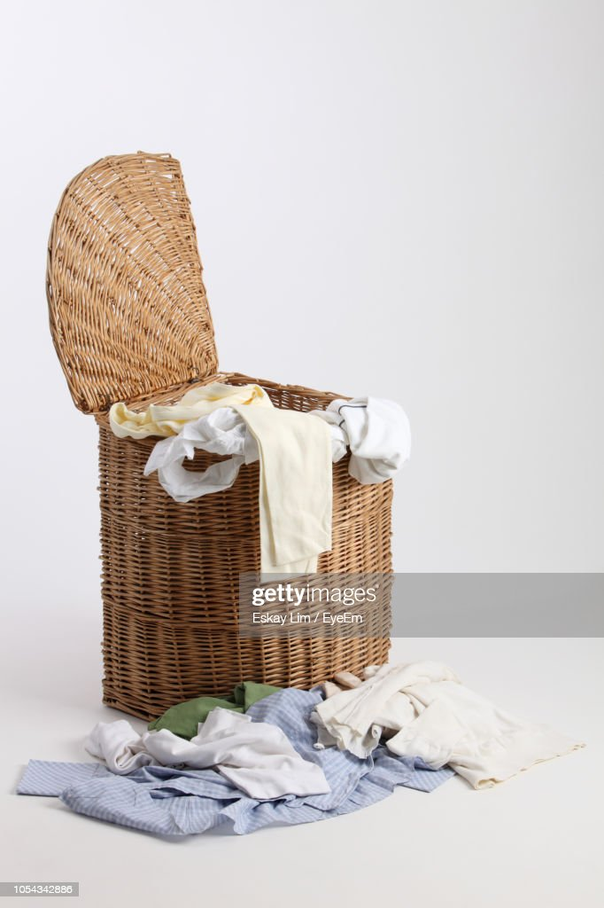 Clothes Falling From Laundry Basket Over White Background : Stock Photo