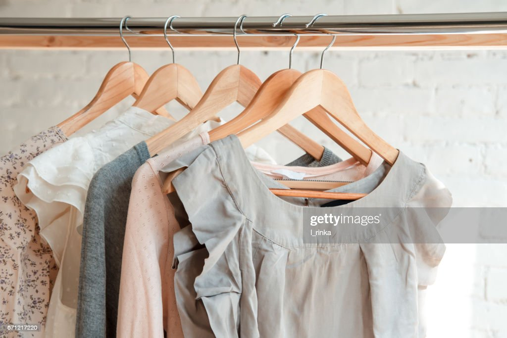 Clothes hang on clothing rack : Stock Photo