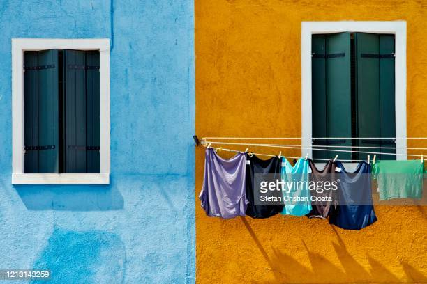 clothes hanged for drying on a window in burano, venice, italy - europa meridionale foto e immagini stock