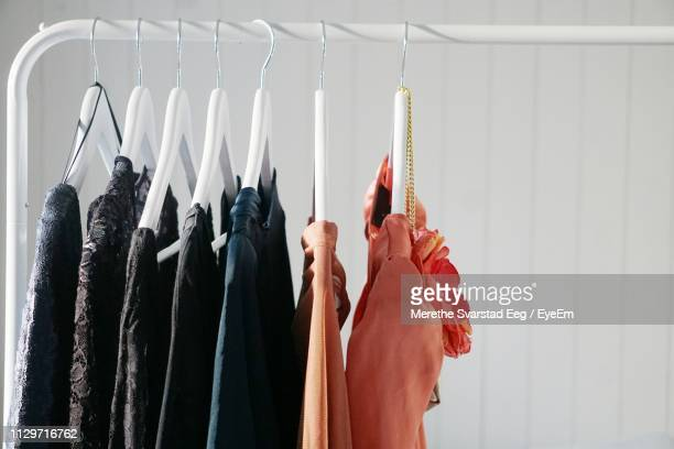 clothes hanging against wall at home - womenswear stock pictures, royalty-free photos & images