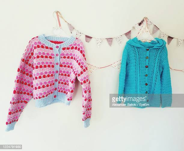 clothes hanging against wall - womenswear stock pictures, royalty-free photos & images