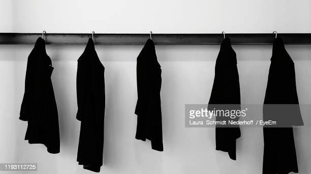 clothes hanging against white wall - laura schmidt foto e immagini stock