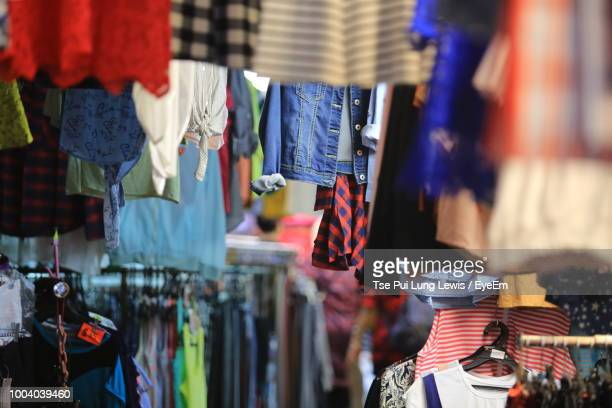 clothes hanging at market stall for sale - fashion hong kong stock photos and pictures
