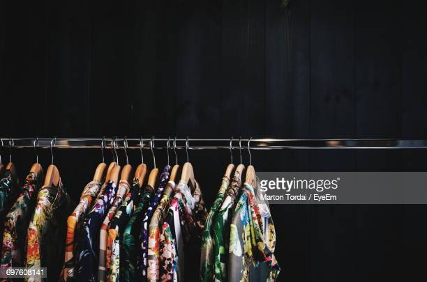 clothes hanging from coathangers on rack against wall in shop - clothes rack stock pictures, royalty-free photos & images