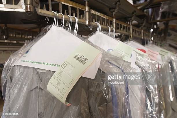 clothes hanging in the laundrette - dry cleaner stock pictures, royalty-free photos & images
