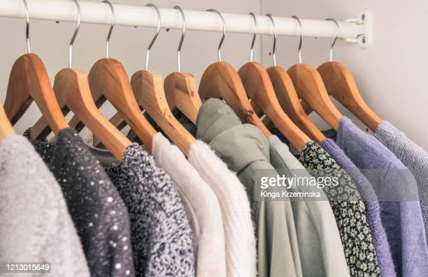 clothes hanging in the wardrobe - 収納ラック ストックフォトと画像