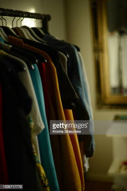 clothes hanging on a hangers by a mirror - kristina strasunske stock pictures, royalty-free photos & images