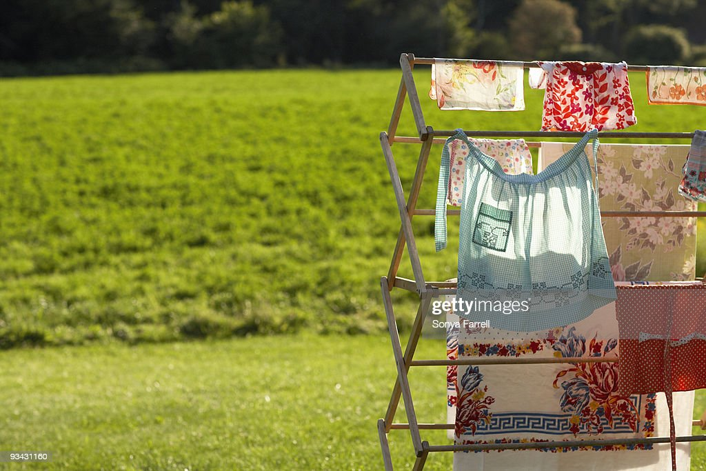 Clothes hanging on drying rack in rural setting : Stock Photo