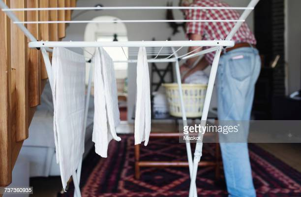 clothes hanging on drying rack while senior man standing in background - 乾かす ストックフォトと画像