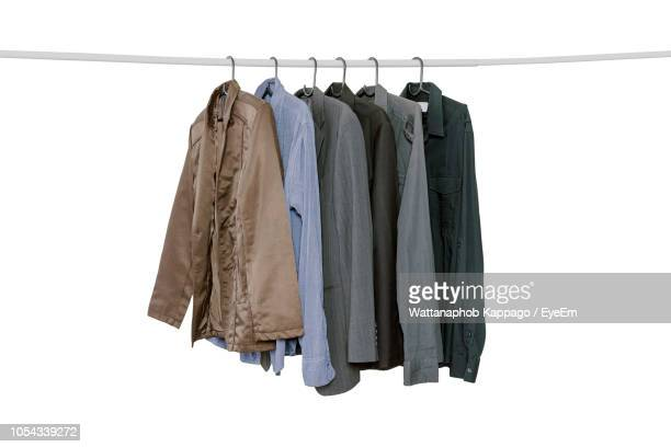 clothes hanging on rack against white background - clothes rack stock pictures, royalty-free photos & images