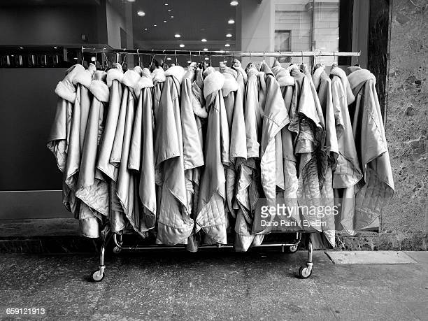 clothes hanging on rack at store for sale - clothes rack stock pictures, royalty-free photos & images