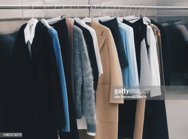 clothes hanging on rack in store - coat photos et images de collection