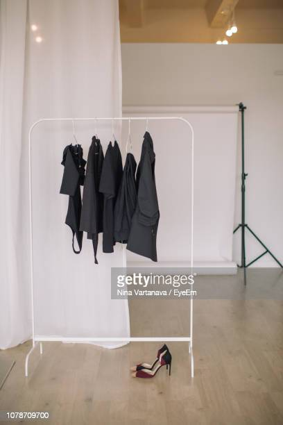 clothes hanging on rack in studio - rack stock pictures, royalty-free photos & images