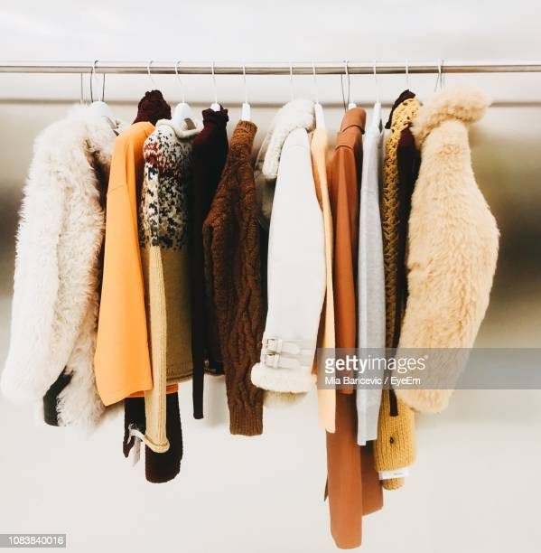 clothes hanging on rack - coat fotografías e imágenes de stock