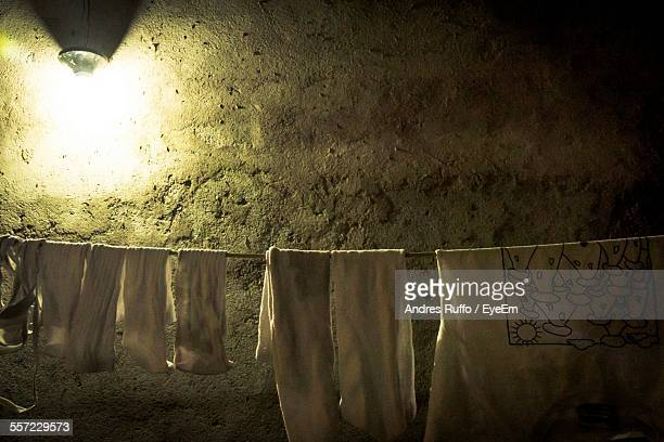 clothes hanging on rope against wall - andres ruffo stock photos and pictures