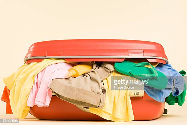 clothes in a suitcase - stuffing stock photos and pictures