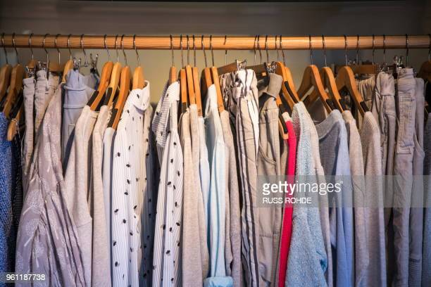 clothes on rail in shop, close-up - clothes rack stock pictures, royalty-free photos & images