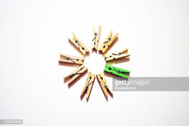 clothes pegs circle with odd green one - clothespin stock pictures, royalty-free photos & images