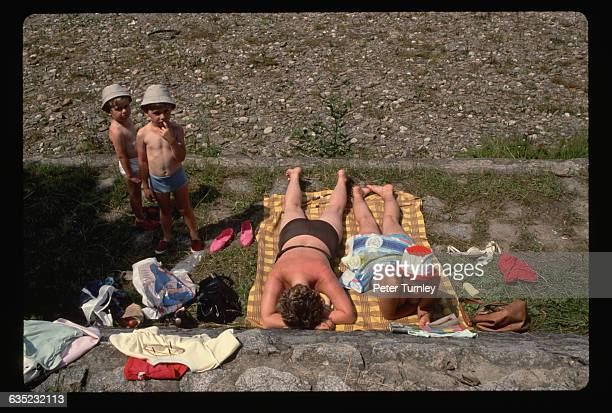 Clothes strewn about them two serious sunbathers relax on a small patch of grass beside uncertain little boys on a lazy summer afternoon