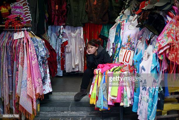 A clothes vendor looks on as she waits for customers in Beijing on March 13 2015 China's consumer inflation rebounded in February from a...
