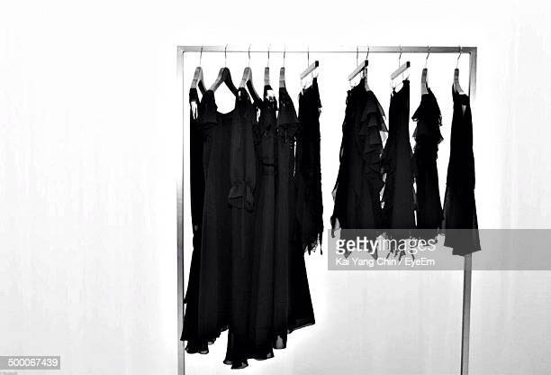 Clothes with hangers on clothing rail against white background