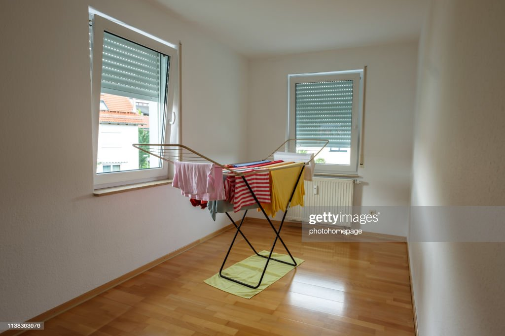 Clotheshores with clothes in a room : Stock Photo