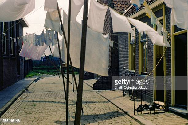 Clotheslines painted homes and a bicycle in the town of Volendam Holland 1952