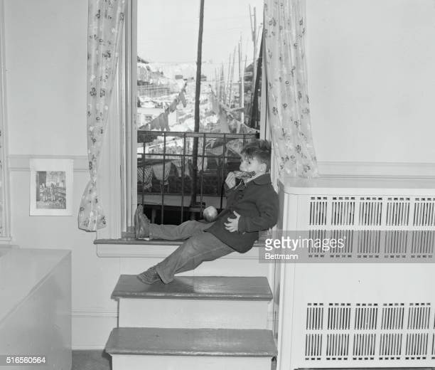 Clotheslines with wash hanging provides backdrop as Nicky enjoys drumstick while sitting on windowsill The children had their turkey a day ahead of...
