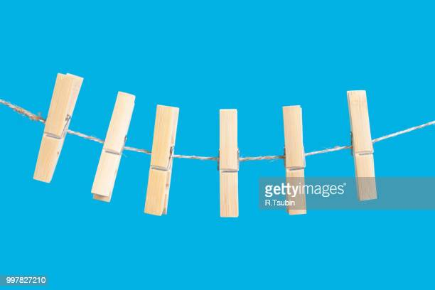 clothespins on rope isolated on blue background - clothespin stock pictures, royalty-free photos & images